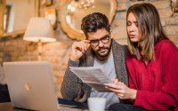 An image of two people reading a bank statement