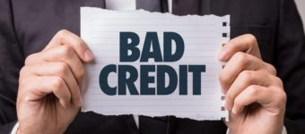 An image of a man holding a bad credit sign