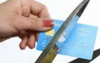 An image of a woman cutting up credit cards