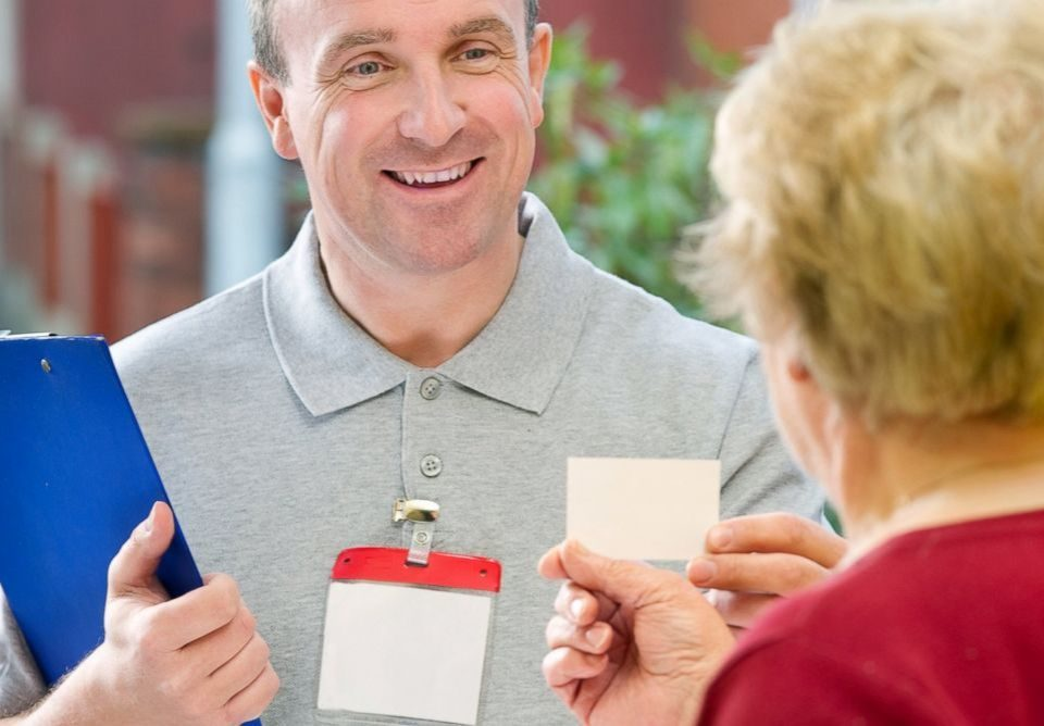an image of a man handing over a card on a doorstep