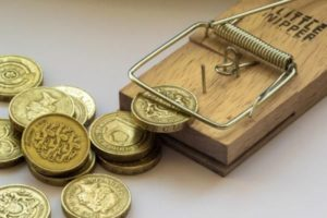 An image of pound coins in a mouse trap