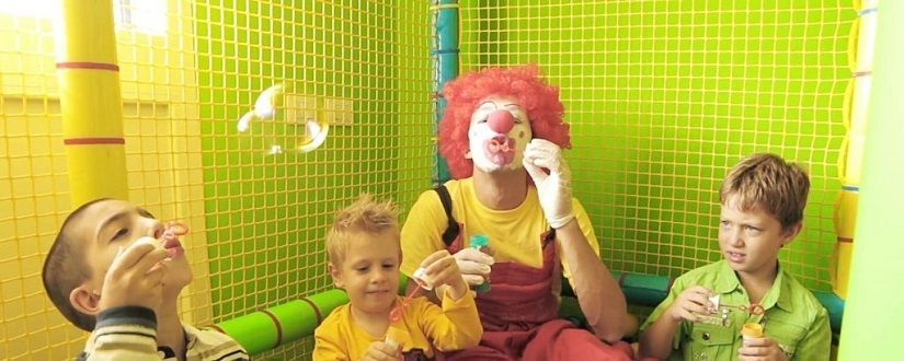 An image of children playing with a clown